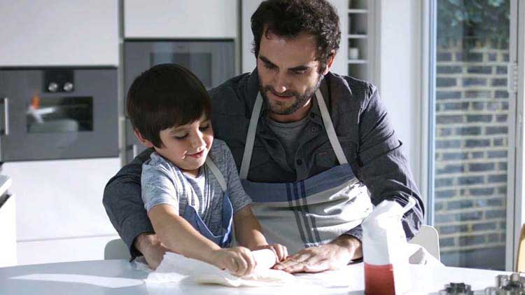Man rolling dough with his child