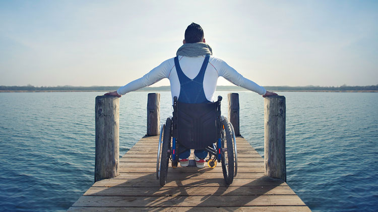 A disabled man sits in his wheelchair on a pier overlooking a lake.