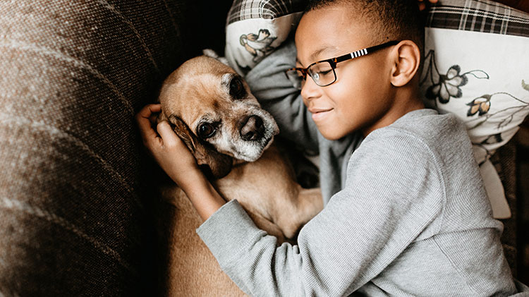 A boy cradles his dog while laying on the couch