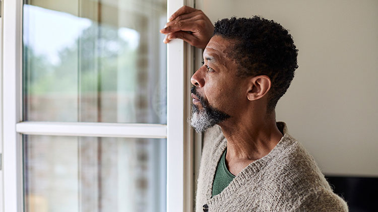 Man looking out the window considering post divorce finances.