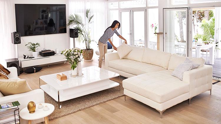 Una mujer arreglando cojines en el sofá mientras prepara una vivienda para la venta.