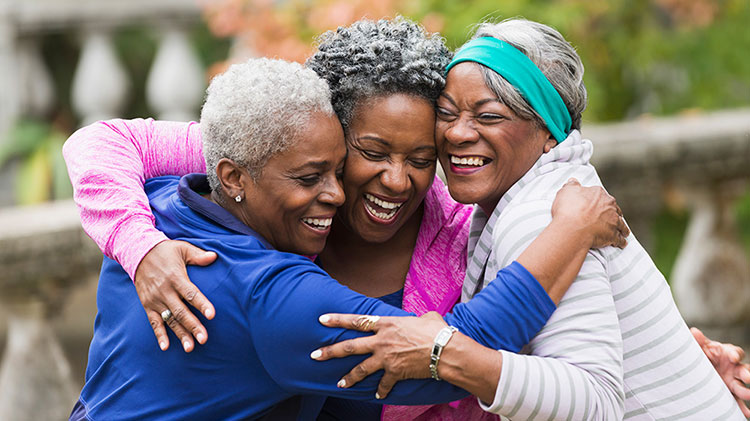 Three women hug and laugh as they enjoy their retirement