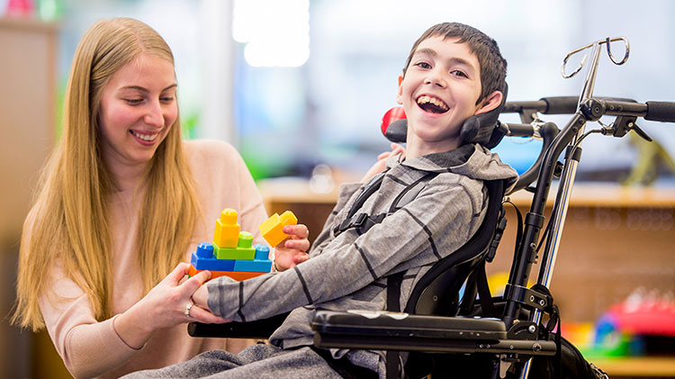 A boy in wheelchair smiles as a woman hands him toy blocks.