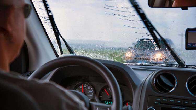 A person driving a car in the rain
