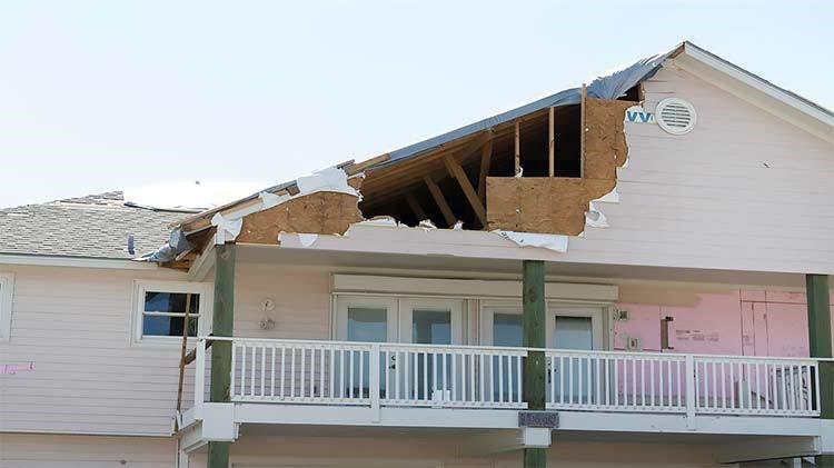 Una casa que le falta una parte del techo a causa de daño por huracán.