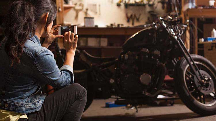 Woman taking a photo of her motorcycle with her phone.