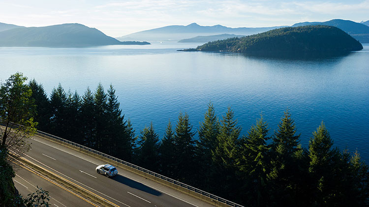 A car is driving down the highway next to a lake and mountains