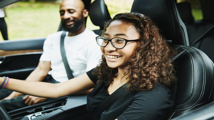 Conductor adolescente sonriendo dentro del carro con su papá