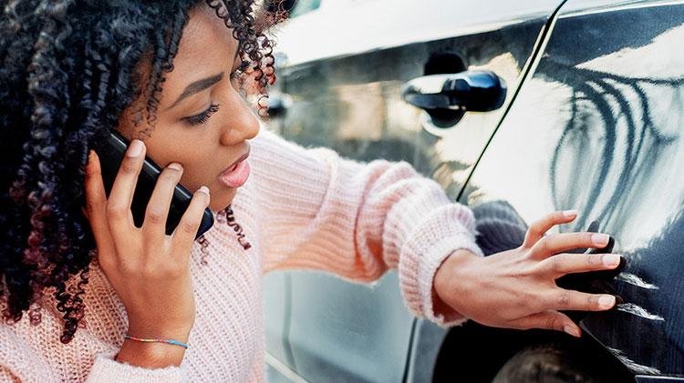 Una mujer llamando a su compañía de seguros para informar de los daños ocasionados al vehículo.