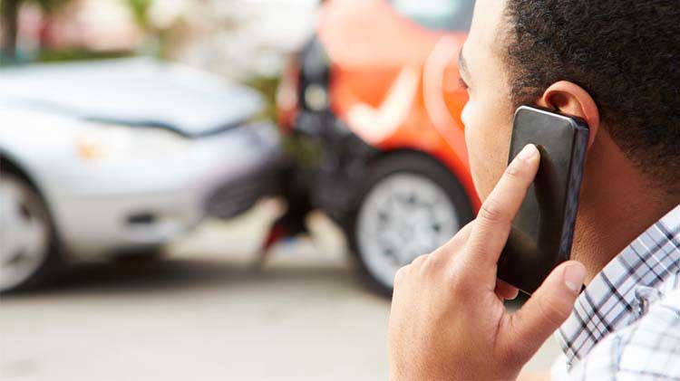 Man on phone call. Car wreck in background.