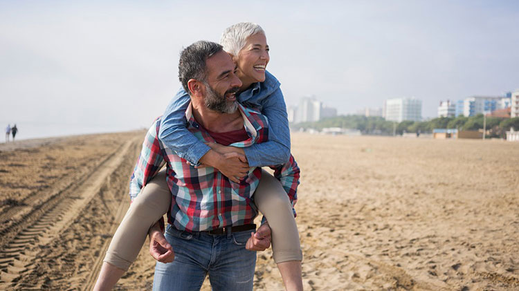 Couple on the beach enjoying the results of their retirement income planning